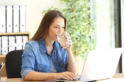 Woman at Laptop drinking ice water.