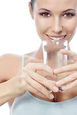 Smiling woman drinking water.
