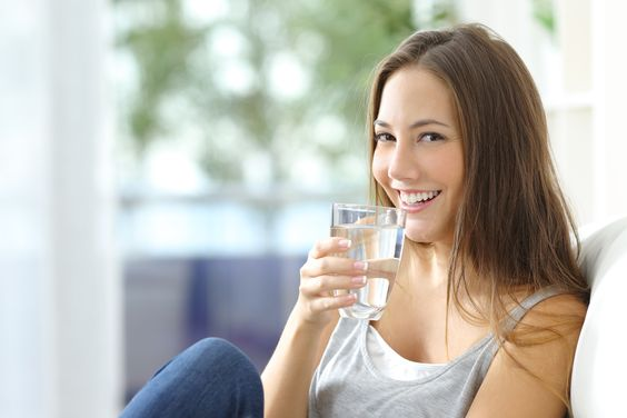 Girl drinking purified water at home.